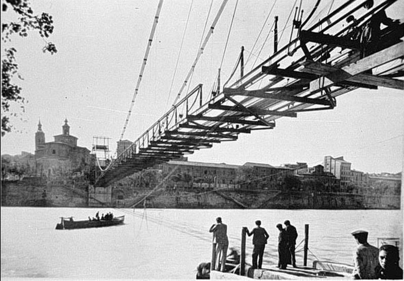 Pasarela peatonal en construcción, en 1940, con la barca con motor del Tío Toni en el río.